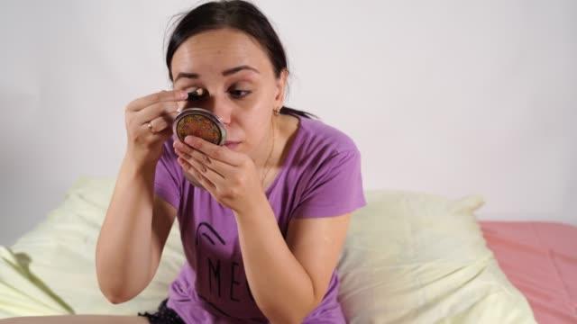 vídeos de stock e filmes b-roll de beautiful woman wearing makeup sitting on bed in bedroom. woman applying make - up sitting on the bed - só mulheres jovens