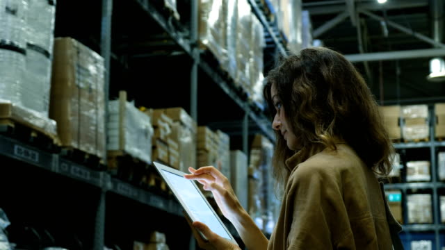 Beautiful woman with a tablet computer pc looking for a product in a storage room video