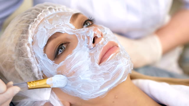 Beautiful woman with facial mask at beauty salon. Spa treatment Beautiful woman with facial mask at beauty salon. Spa treatment. beautician stock videos & royalty-free footage