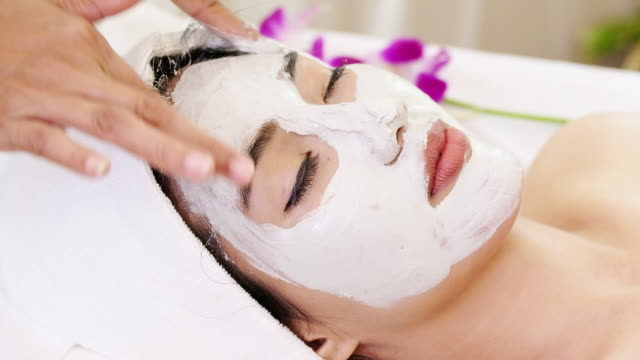 Beautiful woman with facial mask at beauty salon.Applying facial mask at woman face. video