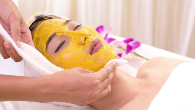 beautiful woman with facial mask at beauty salon.applying facial mask at woman face. - facial stock videos & royalty-free footage