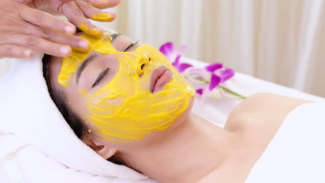 beautiful woman with facial mask at beauty salon.applying facial mask at woman face. - spa facial stock videos & royalty-free footage