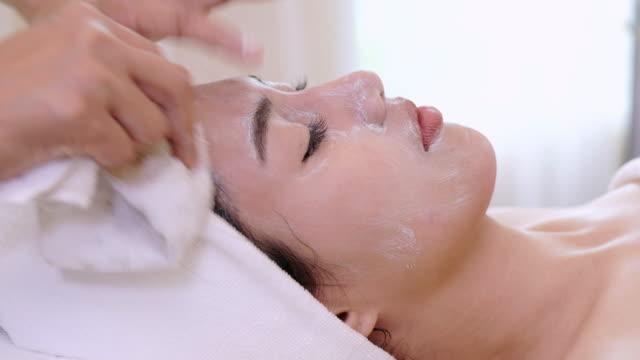 美容院で顔のマスクを持つ美しい女性。女性の顔を顔のマスクを適用します。 - エステ点の映像素材/bロール