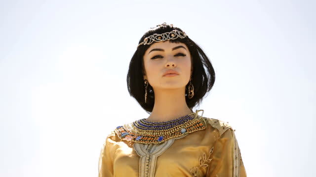 Beautiful woman with fashion make-up and hairstyle like Egyptian queen Cleopatra outdoors against desert windy weather video