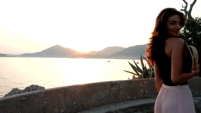 vidéos et rushes de belle femme avec breloques de chapeau et de la dentelle sur l'estran rocheux - mode de la plage