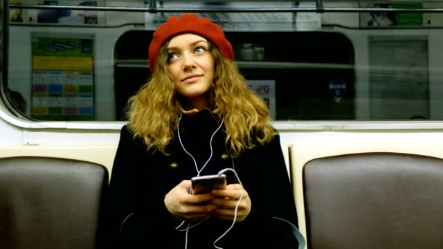 beautiful woman with headphones uses the phone in the subway - music filmów i materiałów b-roll
