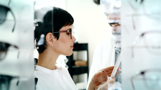 Beautiful woman with optician trying eyeglasses at optics store video