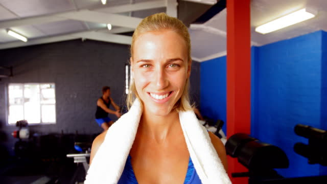 Beautiful woman with towel around her neck standing in gym Portrait of beautiful woman with towel around her neck standing in gym wearing a towel stock videos & royalty-free footage