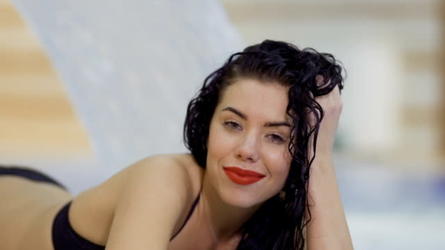 beautiful woman with wet hair flirts with camera - rossetto rosso video stock e b–roll