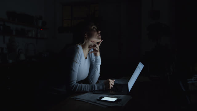 vídeos de stock e filmes b-roll de beautiful woman working late at home using a laptop and receiving text messages on smartphone - important
