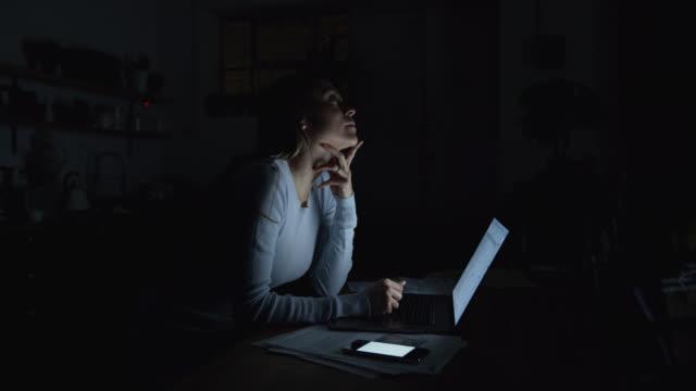 vídeos y material grabado en eventos de stock de hermosa mujer trabajando tarde en casa usando un ordenador portátil y recibiendo mensajes de texto en el teléfono inteligente - urgencia