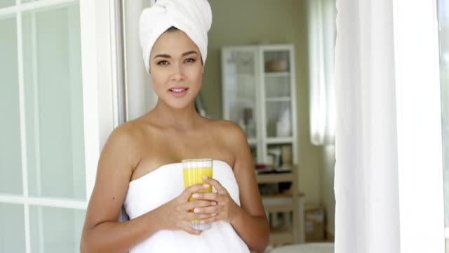 Beautiful woman wrapped in towel looking outside Single beautiful young woman holding glass of orange juice while wrapped in towel and leaning on outside door wearing a towel stock videos & royalty-free footage
