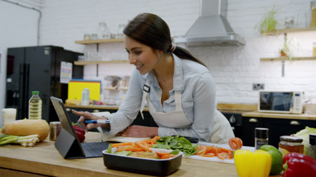vidéos et rushes de belle femme écrivant vers le bas une recette tout en regardant la tablette se penchant sur le compteur de cuisine avec des légumes et d'autres ingrédients - recette