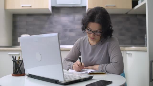 bella donna che scrive in quaderno, lavora al laptop, educazione online - capelli castani video stock e b–roll