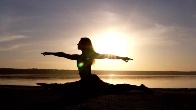 Beautiful woman's silhouette doing yoga, split on sea coast. Morning sunrise, smog sun on thee backstage Beautiful woman's silhouette doing yoga, split on sea coast. Morning sunrise, smog sun on thee backstage. doing the splits stock videos & royalty-free footage