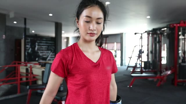 vídeos de stock e filmes b-roll de beautiful women asian boxer happy and fun fitness boxing and punching a bag with wearing boxing gloves.slow motion - boxe tailandês
