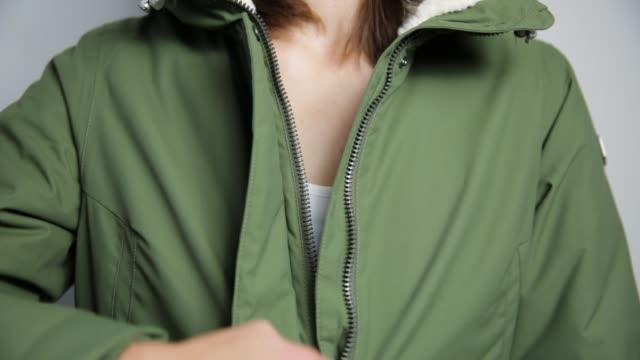 beautiful women closing winter jacket with zipper. - жакет стоковые видео и кадры b-roll