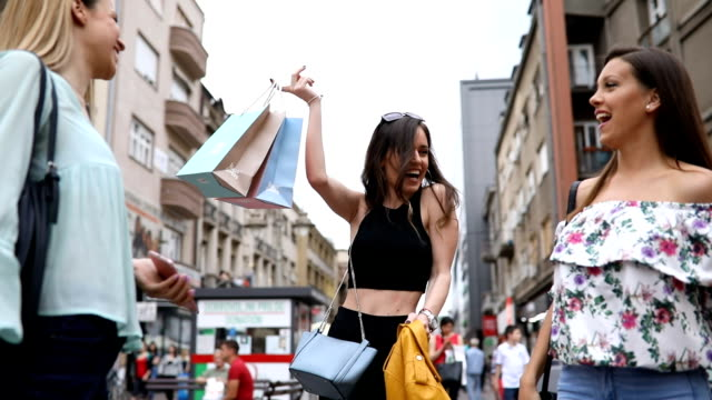 Beautiful women having fun in the city after shopping Lovely and cute young women, having fun together on a city street, while returning from shopping. consumerism stock videos & royalty-free footage