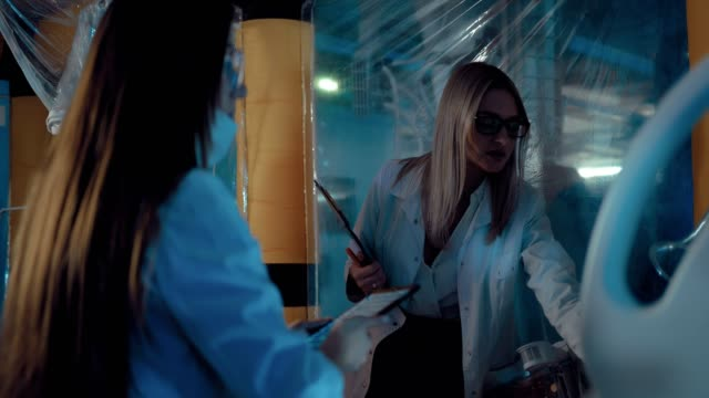 Beautiful women scientists discuss conducting a scientific experiment in a space laboratory. Girls are dressed in white robes and glasses, they enter the data into the tablets.
