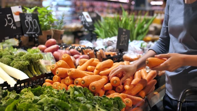 vackra kvinnor shopping morot grönsaker och frukter i stormarknad - grönsak bildbanksvideor och videomaterial från bakom kulisserna