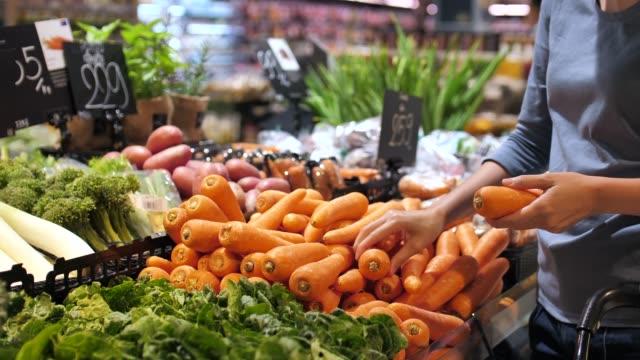 beautiful women shopping carrot vegetables and fruits in supermarket - jarzyna filmów i materiałów b-roll