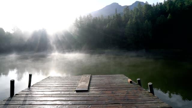 Beautiful wooden lake pier on mountain lake at sunrise, Switzerland video