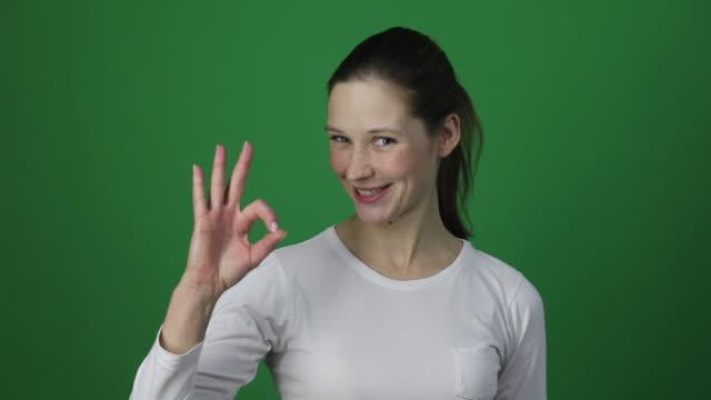 beautiful young adult freckles woman showing ok sign. - znak ok filmów i materiałów b-roll