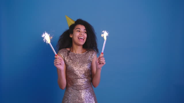beautiful young african curly woman in birthday cap holding two fireworks and have fun