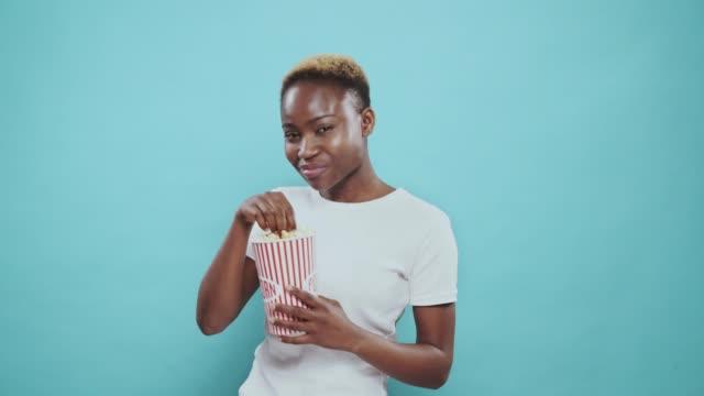 vídeos de stock, filmes e b-roll de menina afro nova bonita que aprecia a pipoca saboroso do balde - balde pipoca