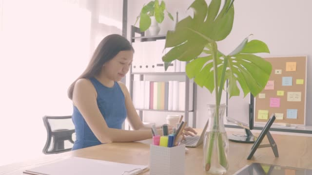 Beautiful young Asian girl working at a home office with a laptop,smartphone and coffee cup on wood table. Concept of female freelancer business.Slow motion.