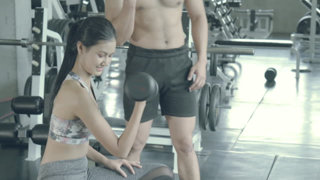 Beautiful young asian woman and coach training workout with strong at gym, asia man teach girl bodyweight with lifting dumbbell at fitness, female strength with exercise, wellbeing and healthy concept.