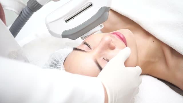 beautiful young asian woman getting ipl and laser treatment by beautician at beauty clinic - kosmetyczka praca w salonie piękności filmów i materiałów b-roll