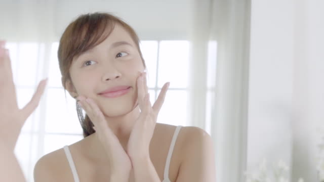 beautiful young asian woman happy applying cream or lotion with moisturizer to skin face, beauty asia girl applying skincare touch facial with cosmetic makeup, healthy and wellness concept. - trattamento per la pelle video stock e b–roll