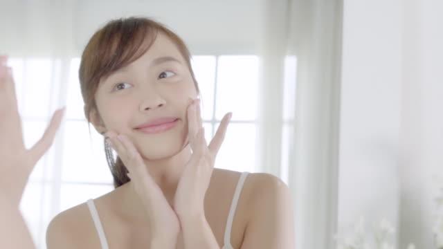 stockvideo's en b-roll-footage met mooie jonge aziatische vrouw gelukkig toepassen crème of lotion met moisturizer aan huid gezicht, schoonheid asia girl toepassing skincare touch facial met cosmetische make-up, gezond en wellness concept. - skincare
