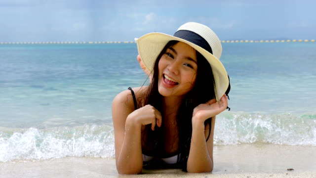 Beautiful young Asian woman in a bikini looking at camera while relaxing lying on beach on summer holidays vacations. Concept freedom, Lifestyle, tourism, holiday.