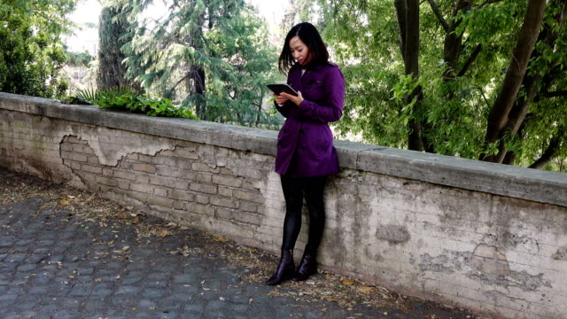 Beautiful young Asian woman leaning against a wall uses the tablet,portrait video
