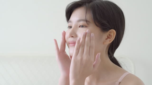 顔の柔らかさのための化粧品の美しい若いアジアの女性のメイクアップ、女の子の手のタッチ顔は、健康、スキンケアと健康コンセプトと完璧な美しさ、若返りのためのクリームとローショ� - スキンケア点の映像素材/bロール