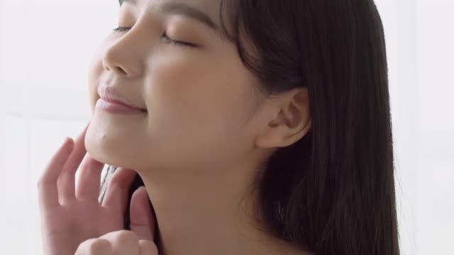 顔の柔らかさのための化粧品の美しい若いアジアの女性のメイクアップ、若返りのためのクリームとローション、ウェルネス、スキンケアと健康コンセプトに最適な美しさのためのクリーム� - 清らか点の映像素材/bロール