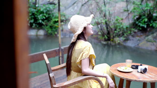 Beautiful young Asian woman relaxing on a wooden chair on the terrace with view of the garden.