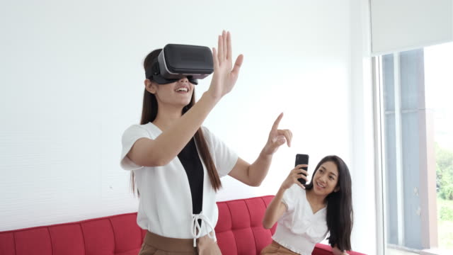 vídeos de stock e filmes b-roll de beautiful young asian woman relaxing playing video games using vr headset and witch one friend using cell phone take a photo sitting on sofa in front of tv at home. having fun. entertainment. - gmail
