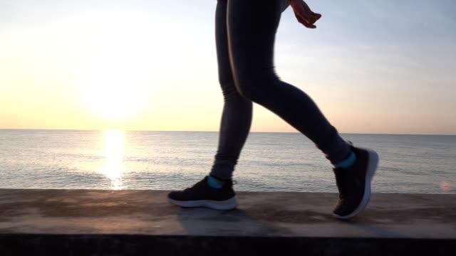 砂浜で走っているスローモーション mo 美しい若いアジアの女性 - 上半身点の映像素材/bロール