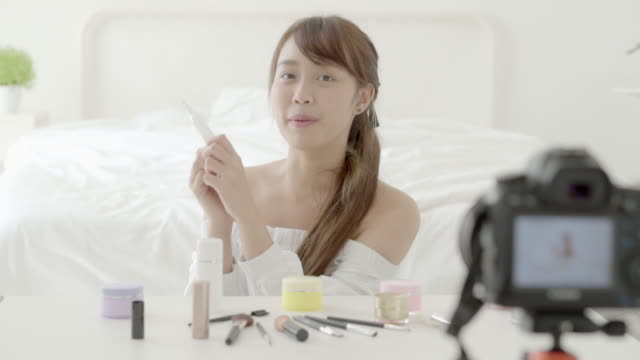Beautiful young asian woman showing cream or lotion the cosmetic makeup with video and vlog at home, beauty girl blogger live review treatment with health on social media online.