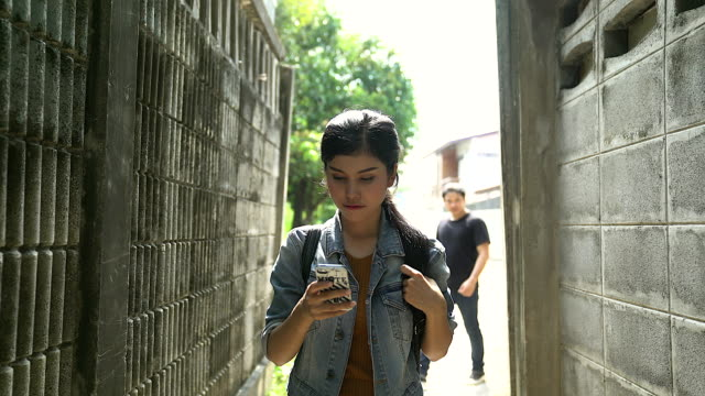 vídeos de stock e filmes b-roll de beautiful young asian woman talking on mobile phone and being stalked by man criminal on the street. - roubar crime