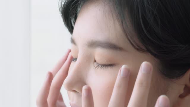 stockvideo's en b-roll-footage met mooie jonge aziatische vrouw aanraking huid glad van de ogen met perfecte, meisje masseren gezicht voor de gezondheid met cosmetische, huidverzorging is hydratatie en verjonging met crème of lotion, schoonheid concept. - aziatische etniciteit