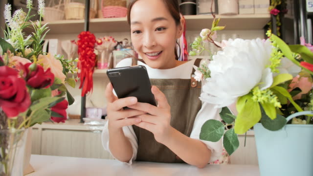 Beautiful young asian woman using smartphone and smiling in flower shop. video