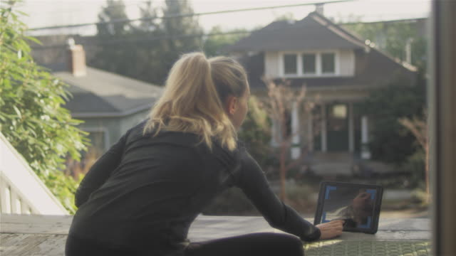 beautiful young asian woman with blonde hair doing some stretches on her porch. using her tablet to look up some instructions. - tappetino video stock e b–roll