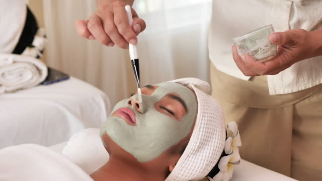 Beautiful young asian woman with facial mask at beauty spa salon. Beauty Treatments, health. 4k video Slow Motion video