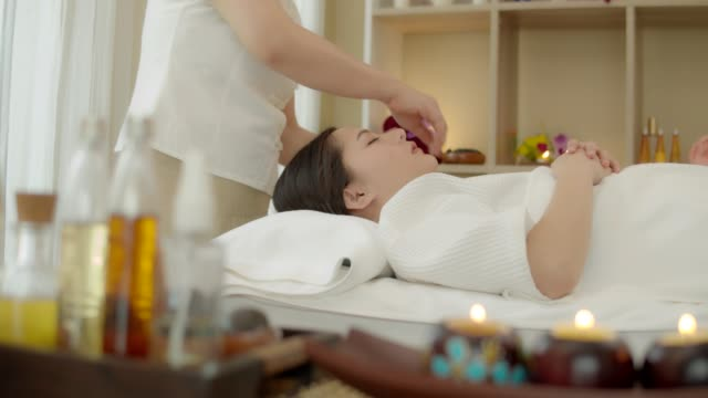 beautiful young asian woman with facial mask ,body massage ,hand and body treatment,foot massage,warm herb massage at beauty spa salon. looking relaxed while getting a massage from a professional masseuse beauty treatments, health. 4k video slow motion. - terapia lastone filmów i materiałów b-roll