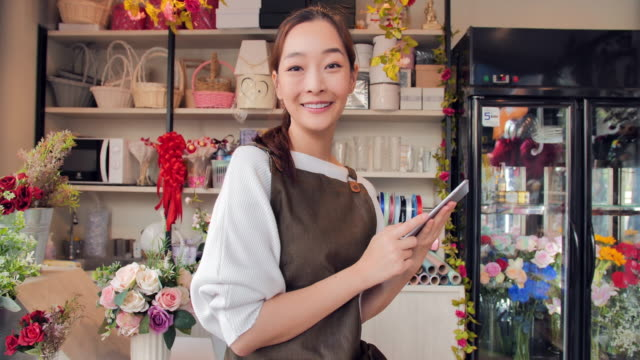 Beautiful young asian woman working using tablet computer and smiling while sitting in workshop. video