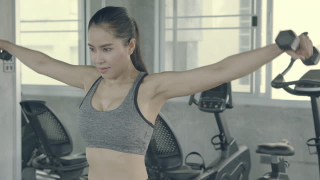 Beautiful young asian woman workout at gym with lifting dumbbell, beauty asia girl training exercise sport with strength muscle arms for bodybuilding at fitness, healthy and wellness concept.